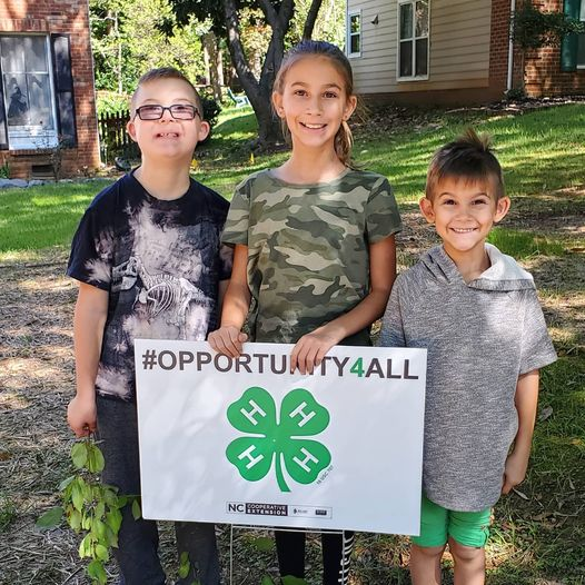 Three youth hold a 4-H #opportunity4all sign in their front yard.